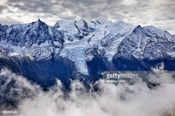 french alps mountain range with snow line. mont blanc summit, peak and glaciers with clouds in valley and overcast sky - pinnacle peak stock pictures, royalty-free photos & images
