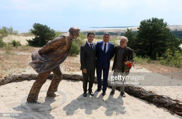 French Ambassador to Lithuania Philippe Jeantaud sculptor Klaudijus Pudymas and the Mayor of Neringa Darius Jasiatis pose next to a bronze statue...