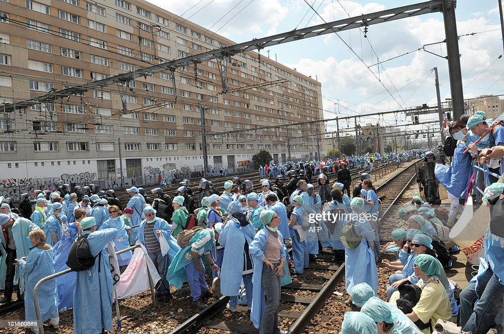 French anaesthetist nurses stand on tracks near the Montparnasse train station on May 18, 2010 in Paris, during a demonstration blocking the speed train (TGV) traffic, to protest against their work conditions.