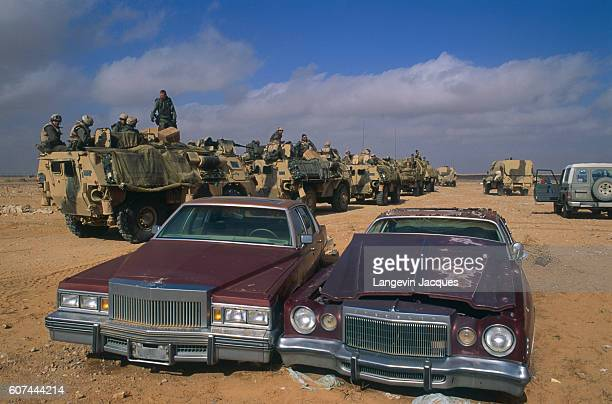 French and American troops pass destroyed cars while moving along the Iraqi border during the Persian Gulf War In August of 1990 Iraqi president...