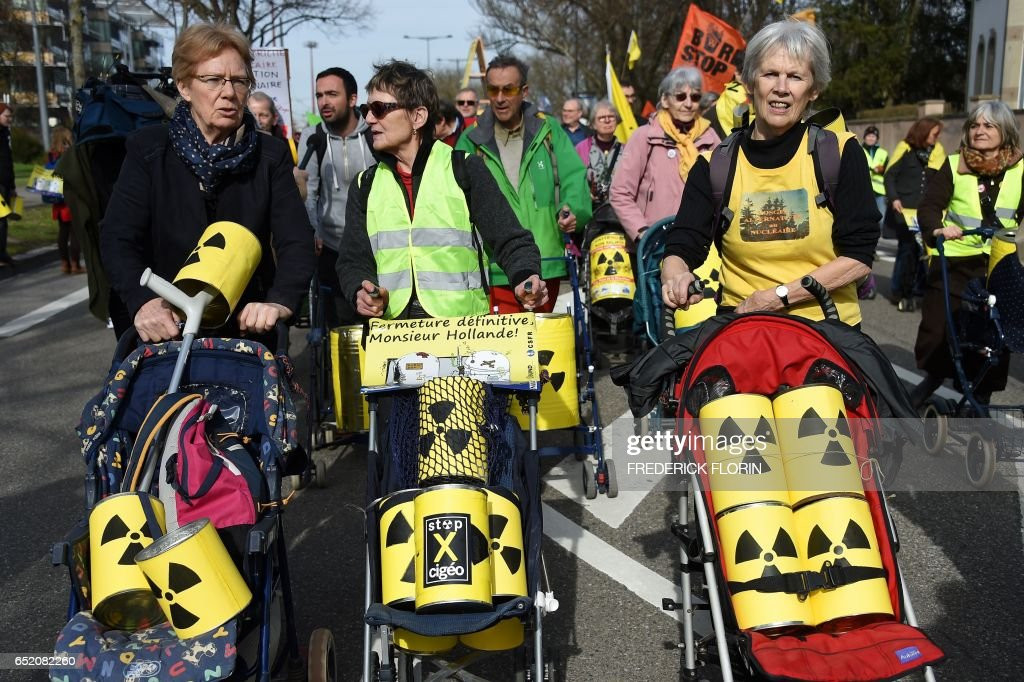 French and German anti-nuclear activists push strollers as they take part in the commemoration of the nuclear disaster in Fukushima and protest against the nuclear powerplant of Fessenheim, France's oldest nuclear reactor on March 11, 2017 in Strasbourg, eastern France. Fessenheim, located on a seismic fault line, has worried French, German and Swiss environmentalists for years and its fate has been the subject of dispute with Berlin. /