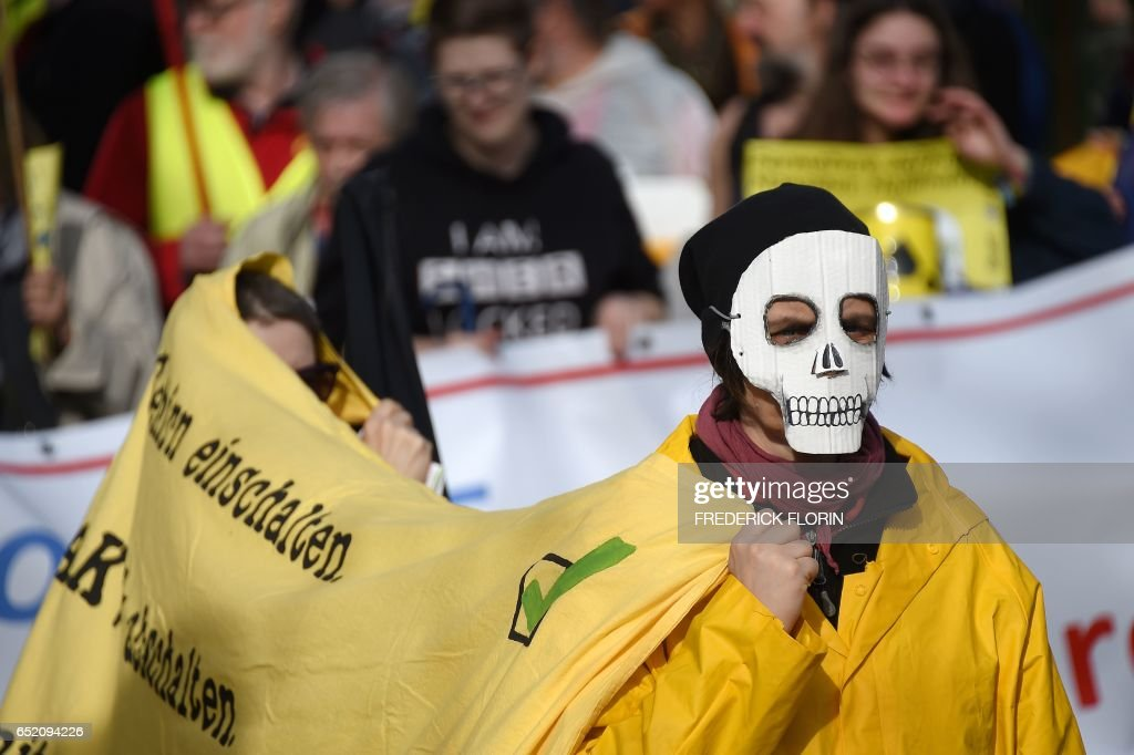 French and German anti-nuclear activists take part in the commemoration of the nuclear disaster in Fukushima and protest against the nuclear powerplant of Fessenheim, France's oldest nuclear reactor on March 11, 2017 in Strasbourg, eastern France. Fessenheim, located on a seismic fault line, has worried French, German and Swiss environmentalists for years and its fate has been the subject of dispute with Berlin. /