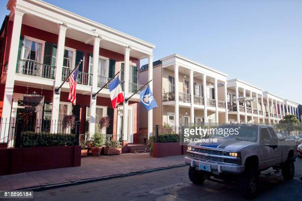 US French and Louisiana flags seen flying outside a row of traditional buildings New Orleans Louisiana USA