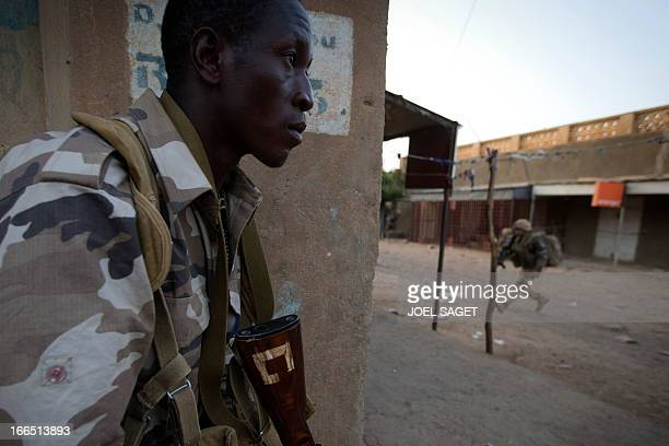 French and Malian soldiers take position after a wrong alert by the population signaling Mujaho's members in a street in Gao on April 13 2013 Gao...