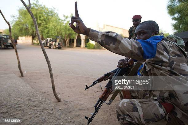 French and Malian soldiers take position during a wrong alert by the population signaling Mujaho's members in a street in Gao on April 13 2013 Gao...