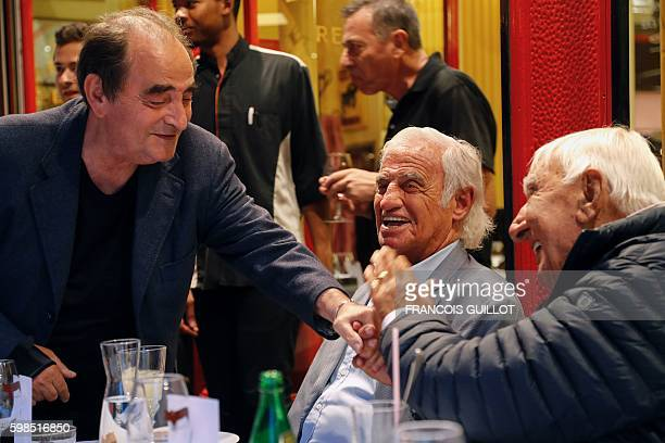 French and Senegalese actor Richard Bohringer shakes hands with French actor Charles Gerard next to French actor Jean-Paul Belmondo who's being...