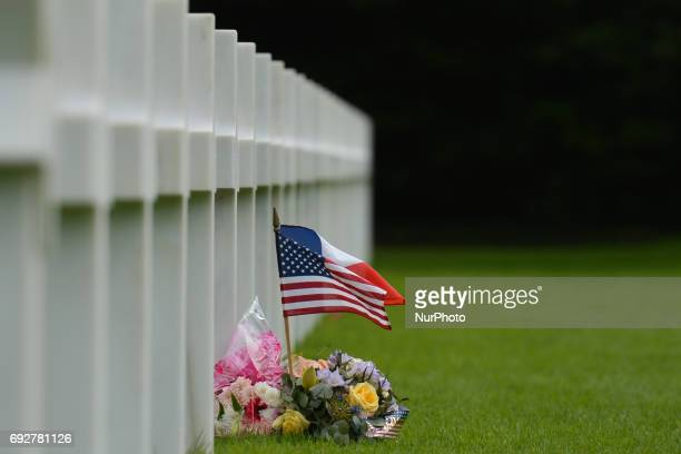 French and US flags near the graves of fallen soldiers at the Normandy American Cemetery that contains the remains of 9,387 American military dead,...