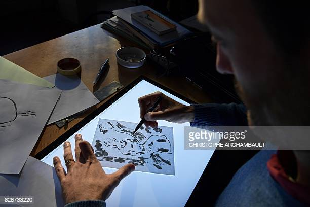 French animation film designer Sebastien Laudenbach draws in his workshop in Paris on November 30 2016 'The young woman without hands' is the first...