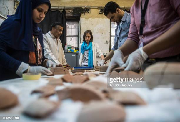 French Anita Quiles a researcher in the French Institute of Eastern Archaeology in Cairo stands near local staff at a dating laboratory inside the...