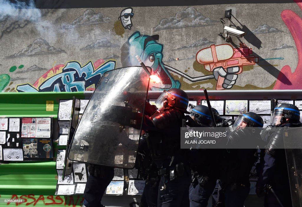 TOPSHOT - French anti riot police react as a smoke bomb is thrown during a clash with protesters during the traditional May Day demonstration in Paris on May 1, 2016. / AFP / ALAIN