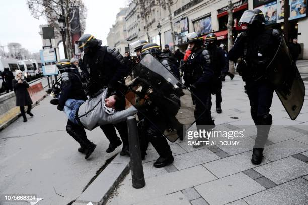 French anti-riot CRS police officers arrest a man on the Champs Elysee avenue, on December 29, 2018 during a demonstration called by the yellow vests...