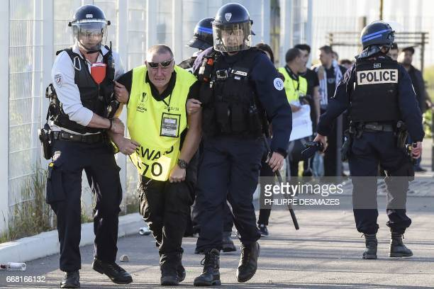 French antiriot Gendarmes evacuate a steward injured by Besiktas supporters during clashes outside the Parc Olympique Lyonnais stadium prior to the...