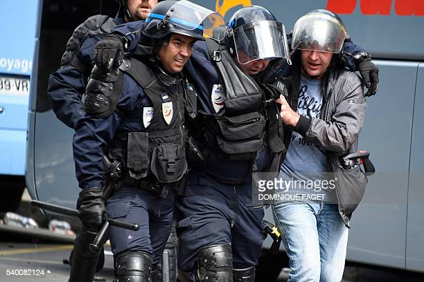A French antiriot police officer is helped by colleagues as they walk during a demonstration against proposed labour reforms in Paris on June 14 2016...