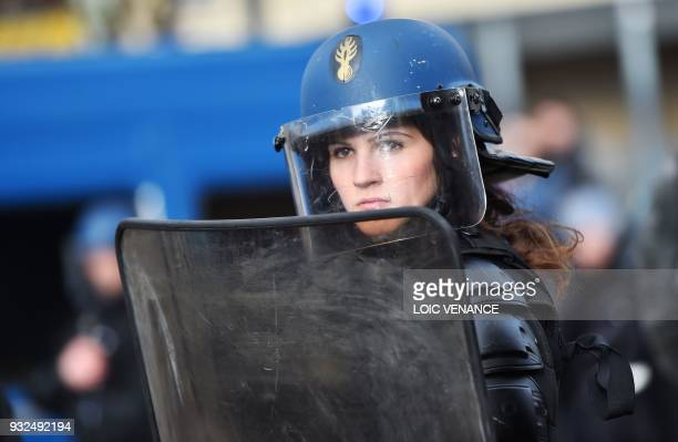 A French antiriot police officer looks on as students and far left activists protest on March 15 2018 in Nantes as part of a national day of action...