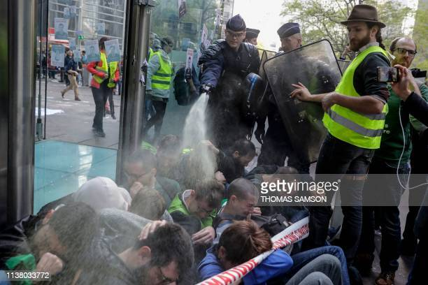 A French antiriot police officer uses pepperspray on climate change activists as they block the entrance of the Societe Generale bank headquarters...