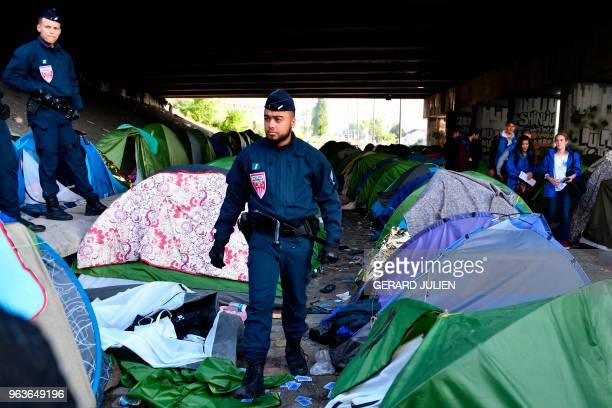 French antiriot police officers inspect the tents left behind by migrants following the evacuation of the Millenaire makeshift camp along the Canal...