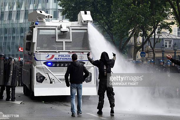 TOPSHOT French antiriot police officers spray water from a vehicle to protesters gesturing during a demonstration against proposed labour reforms in...