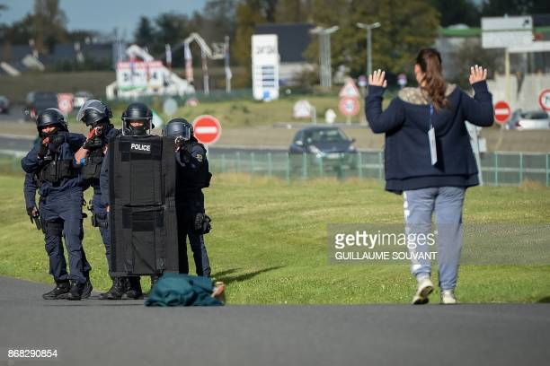 French antiriot police officers stand guard as a woman runs in their direction during an exercise simulating a terrorist attack inside the theatre...