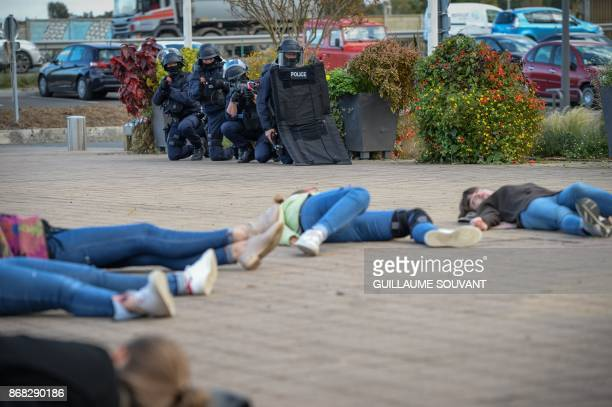 French antiriot police officers stand guard by victims lying on the ground as they prepare an evacuation of the hostages during an exercise...