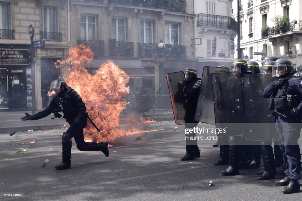 A French anti-riot policeman throws a tear gas canister as a fire burns next to him while French anti-riot policemen stand guard as they patrol and clash with protesters during a march for the annual May Day workers' rally in Paris on May 1, 2017. /