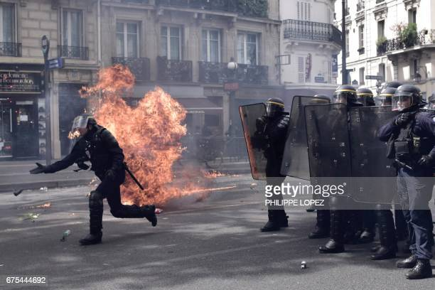 A French antiriot policeman throws a tear gas canister as a fire burns next to him while French antiriot policemen stand guard as they patrol and...
