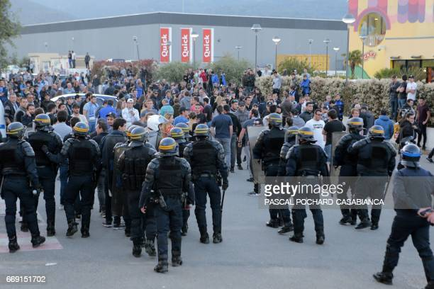 French antiriot policemen stand guard the stadium exit as Bastia's supporters wait for the Lyon's players coach to leave after the French L1 football...