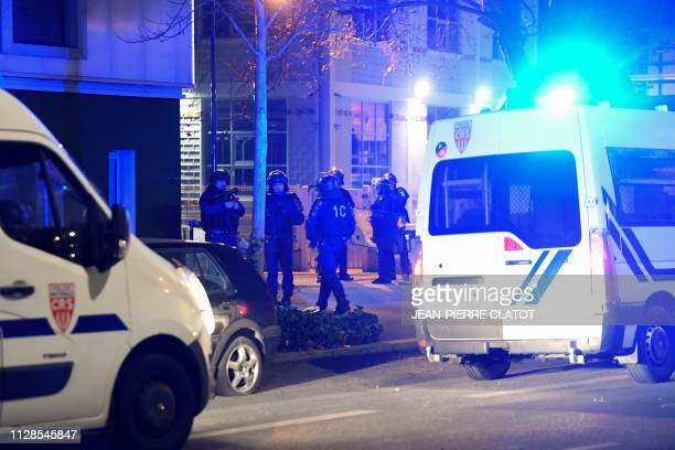 French antiriot policemen stand next to police trucks in the street where riots sparked on March 3 2019 following the death of 2 young people on a...