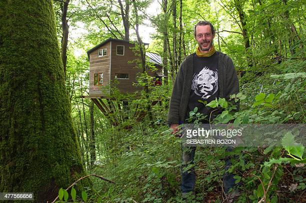French arborist Xavier Marmier poses for photographs in front of his tree house or 'ecological house' on June 16 2015 in Cleron eastern France...