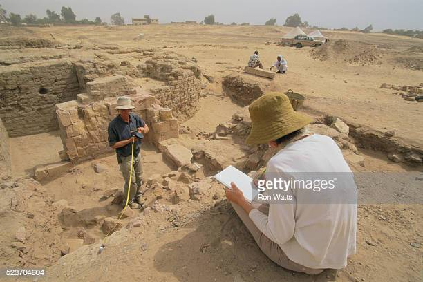 french archaeologists taking notes at dig site - archäologie stock-fotos und bilder