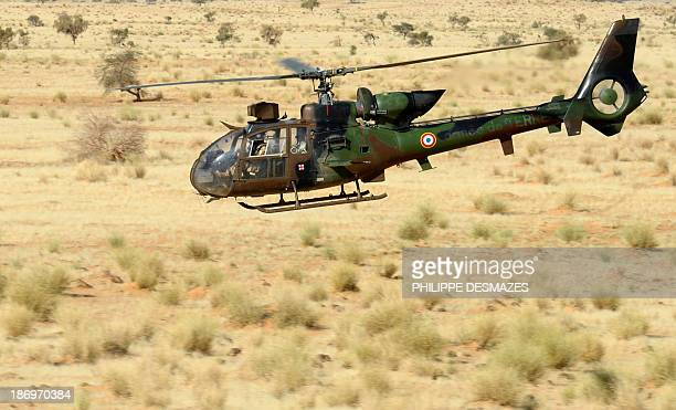 A French army helicopter Gazelle flies over the desert during the Hydra Operation on October 29 near the village of Bamba between Timbuktu and Gao...
