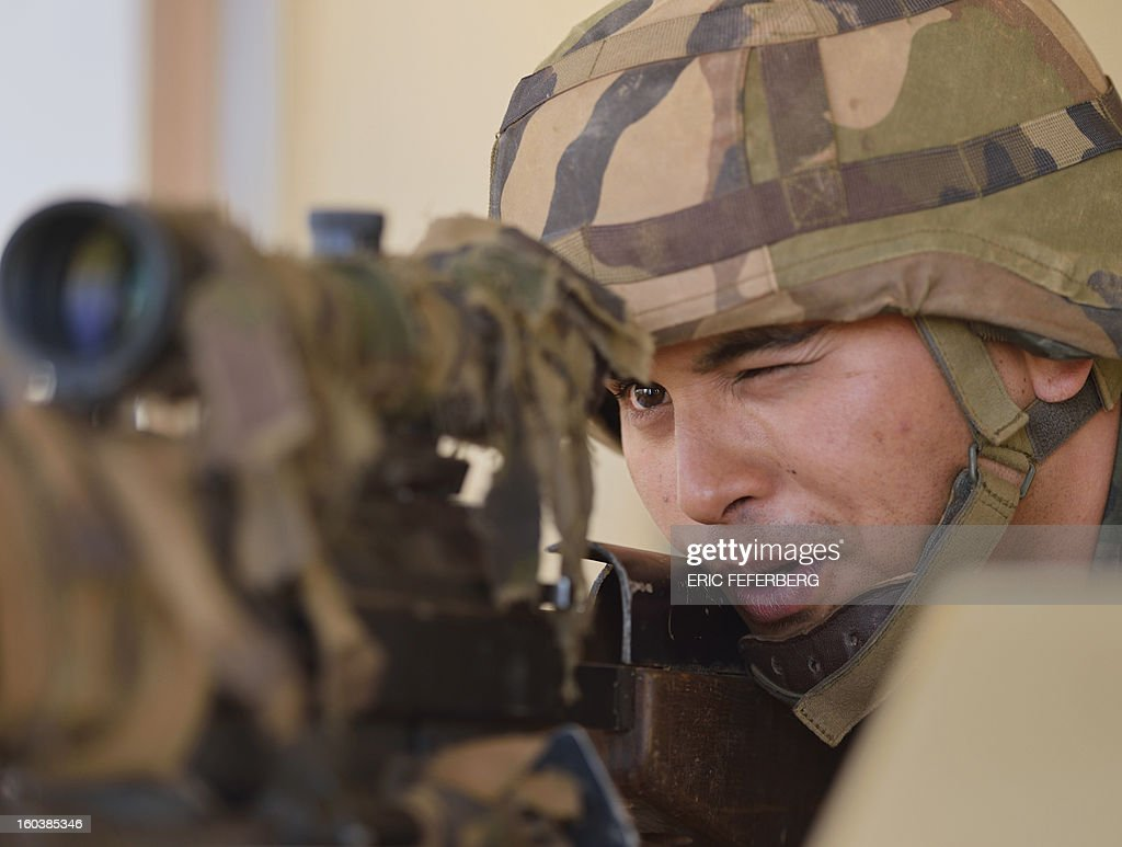 A French army sniper stands guard with his FR 12'7 PGM gun as he looks out from the watchtower at the airport in Timbuktu, on January 30, 2013. French troops have taken up position today at the airport in Kidal, local sources said, the third major city in northern Mali after Gao and Timbuktu.