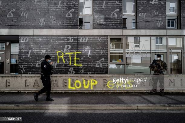 French army soldier stands guard as a police officer walks by outside the National Armenian Memorial Centre in Decines-Charpieu, near Lyon, on...