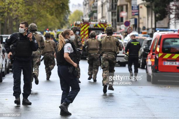 French army soldiers rush to the scene after several people were injured near the former offices of the French satirical magazine Charlie Hebdo...