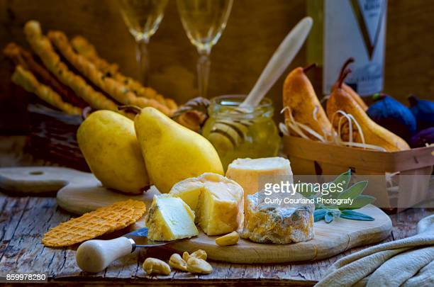 French artisanal goat cheese Crottin de Chavignol made in Ukrainian farm with pears, grissini bread sticks, waffles, honey, figs, white wine, sage and cashew