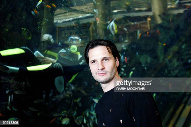 French artist Christophe Petyt poses 30 March 2005 in front of the huge aquarium of Dubai's luxurious Burj alArab hotel where he will have an...