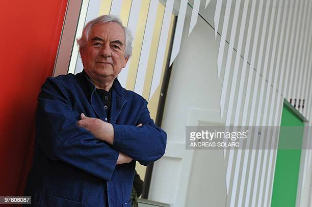French artist Daniel Buren poses in front of an in situ installation at the Macro museum in Rome on March 10 2010 The installation triangles and...