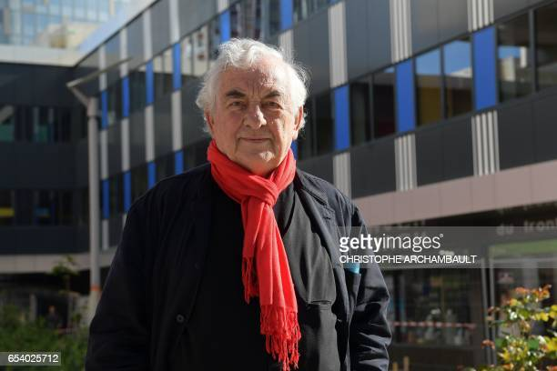 French artist Daniel Buren poses on March 16 2017 in Paris in front of the YoomaUrban Lodge hotel which has on its facade his trademark vertical...