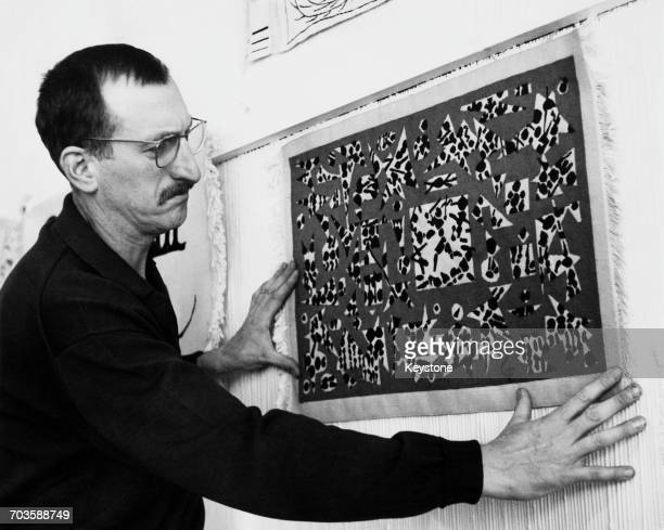 French artist Jacques Lagrange hanging one of his tapestries entitled 'The Death of Simon de Montfort' at the ICA in Dover Street London 11th October...