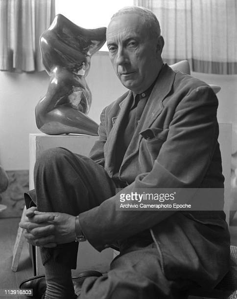 French artist Jean Arp sitting to the floor in front of a sculpture of his fullfigured portrayed wearing a corduroy blazer Paris 1948