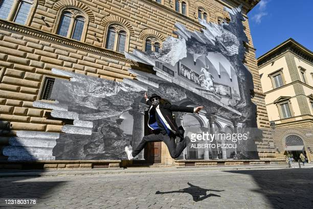"""French artist JR jumps as he poses during the unveiling of his visual installation """"La Ferita"""" on the facade of the Renaissance Palazzo Strozzi in..."""