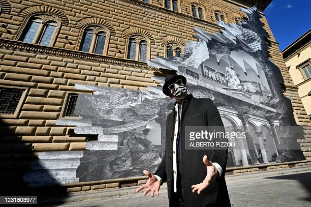 """French artist JR poses during the unveiling of his visual installation """"La Ferita"""" on the facade of the Renaissance Palazzo Strozzi in Florence on..."""