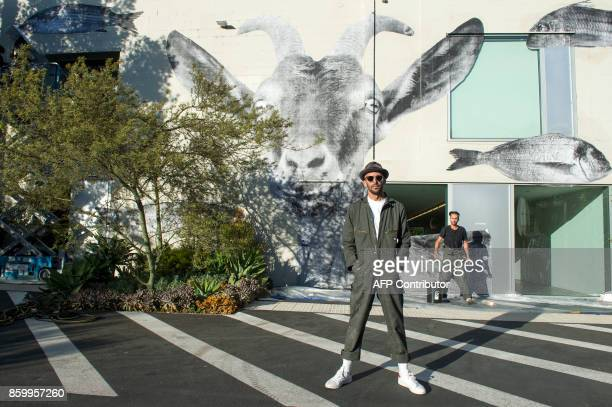 French Artist JR poses infront of his pasting of a goat and fishes on the wall of Blum and Poe Gallery on October 10 in Los Angeles California / AFP...