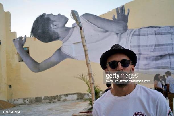 French artist JR poses near his work of an Image called Giants of a boy looking over a wall during the 13th Havana Biennial on April 13 2019 in...