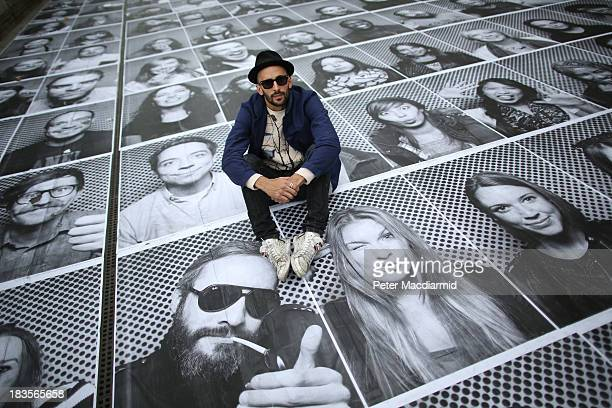 French artist 'JR' poses with some of his giant portraits at Somerset House for his Inside Out project on October 7 2013 in London England Displaying...