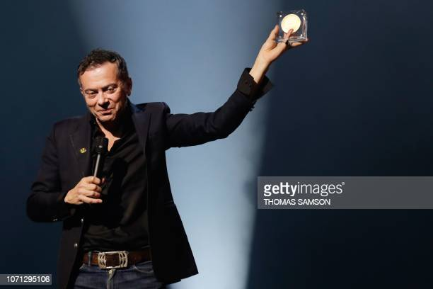 French artist Pascal Parisot celebrates after receiving the 'young audience directory' award during the SACEM Grand Prix awards ceremony on December...