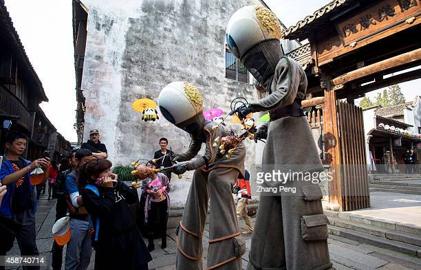 WUZHEN TONGXIANG ZHEJIANG CHINA French artists are dressed up as huge robots and parade on stilts through the ancient street The second Wuzhen...