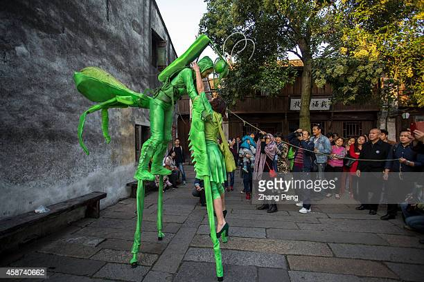 WUZHEN TONGXIANG ZHEJIANG CHINA French artists are playing stilts parade named 'Mantis world' through the ancient street The second Wuzhen Theater...