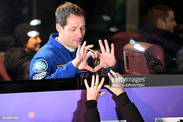 TOPSHOT French astronaut Thomas Pesquet gestures a heart shape from inside a bus as he leaves to board the Soyuz MS03 spacecraft at the Russianleased...