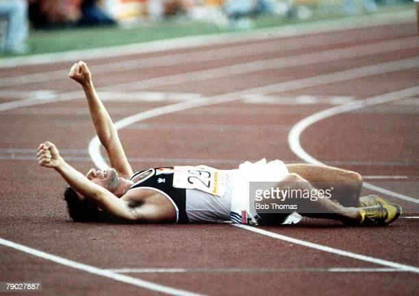 French athlete Joseph Mahmoud lies on the track and raises his arms in the air in celebration after finishing in second place to win the silver medal...