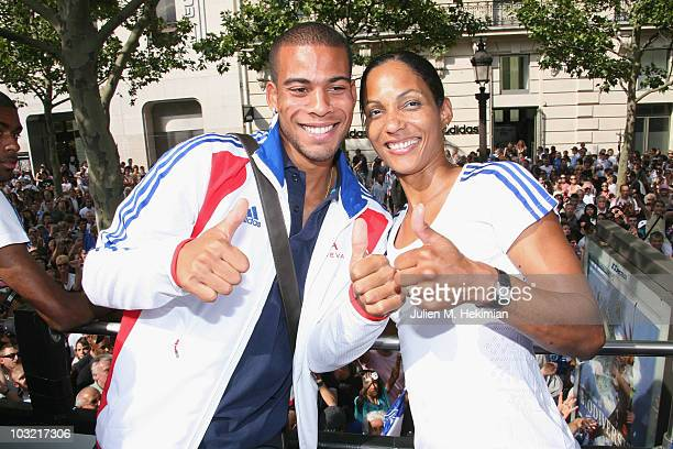 French athletes Benjamin Compaore and Christine Arron pose as they leave the official sponsor store Adidas on the Champs Elysees avenue in Paris on...